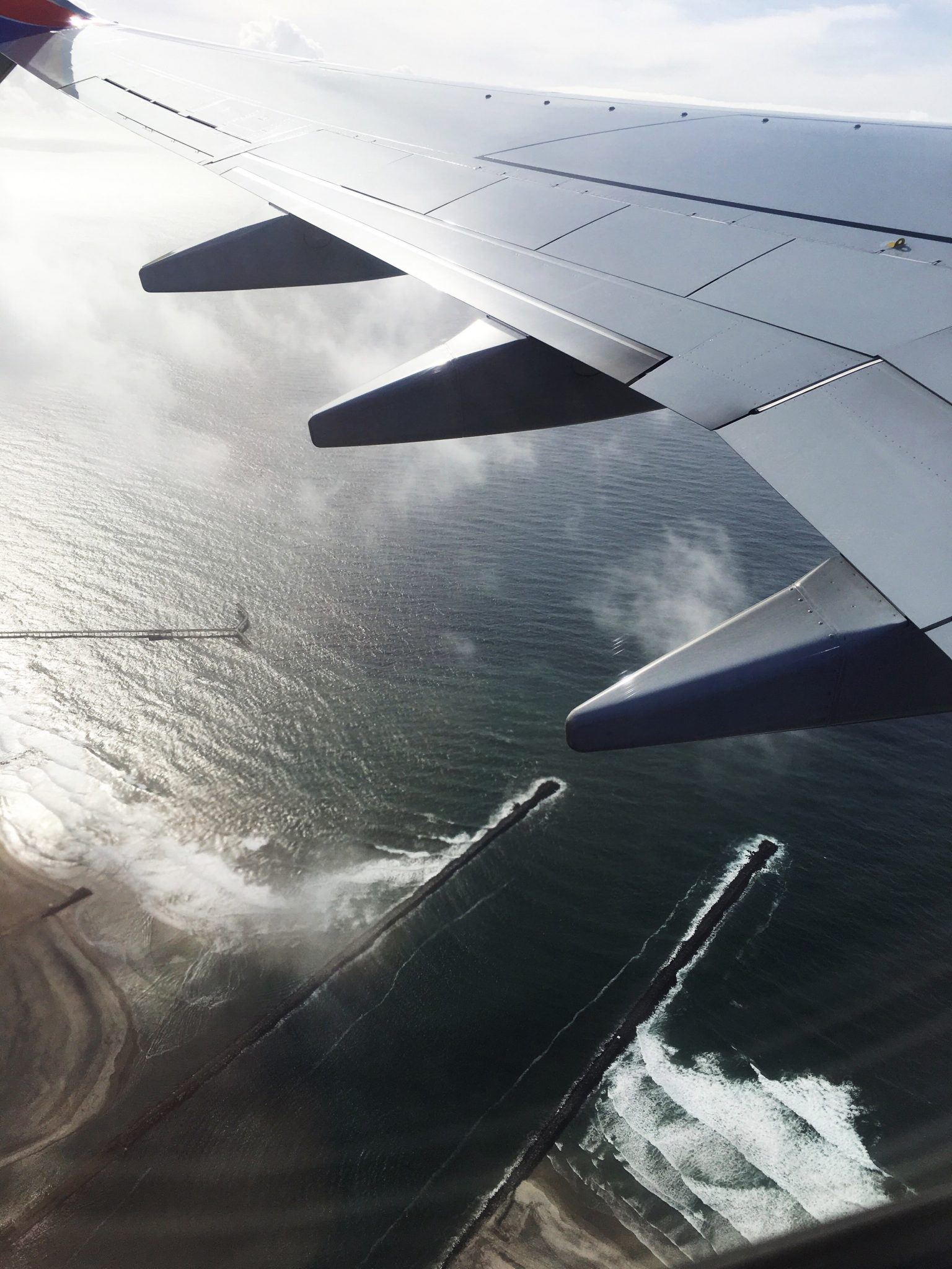 Travel Trip - Captured plane wing, flying over the Pacific Ocean near San Diego, California